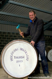 Wolfburn Distillery Production Manager Shane Fraser hammers the bung into the distillery's first barrel of new make spirit , January 2013.