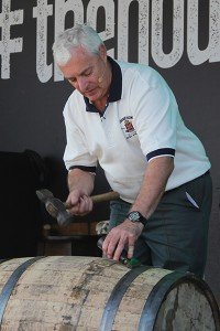 Ger Buckley, Midleton Distillery's 5th generation cooper, demonstrates the breaking down of a barrel during The Housewarming celebration at Midleton September 4, 2013. Image ©2013 by Mark Gillespie.