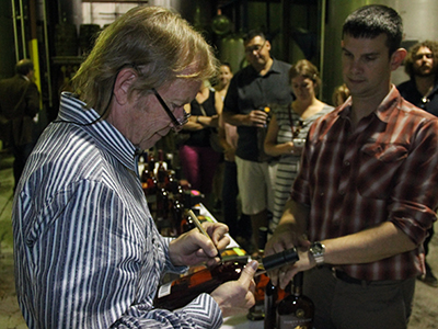 John Hall signs a bottle of Forty Creek Heart of Gold Canadian Whisky at the distillery on September 28, 2013. Image © 2013 by Mark Gillespie.
