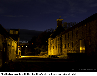 The Mortlach Distillery at night, with the former maltings and kiln shown at right. Photo ©2013 by Mark Gillespie.
