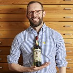 Illustrator Dermot Flynn with the 2014 Jameson St. Patrick's Day bottle. Image courtesy Irish Distillers.
