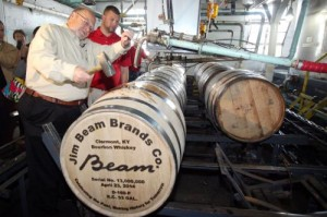 Fred Noe and his son, Freddie Noe, hammer in the bung on Beam's 13 millionth barrel of whiskey since the end of Prohibition in 1933 during a ceremony in Clermont, Kentucky. Photo courtesy Beam.