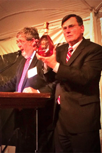 DISCUS President & CEO Adm. Peter Cressy holds the Bill Clinton-signed bottle of George Washington's Rye during the Spirit of Mount Vernon auction October 14, 2014. Photo courtesy DISCUS.
