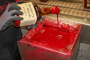 A Maker's Mark Distillery worker hand-dips a bottle in the brand's traditional red wax. File photo ©2008 by Mark Gillespie.