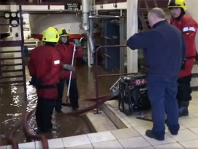Glencadam Distillery manager Douglas Fitchett and firefighters look over flooding in the still house on January 7, 2016. Photo courtesy STV News.