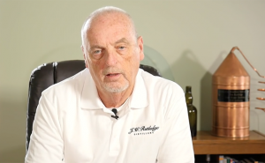Jim Rutledge describes his distillery project in a video on the distillery's web site. His Bourbon Hall of Fame still is over his left shoulder. Image courtesy J.W. Rutledge Distillery LLC.