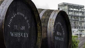 Whiskey barrels at Ireland's Midleton Distillery with the distillery in the background. Photo ©2013, Mark Gillespie/CaskStrength Media.