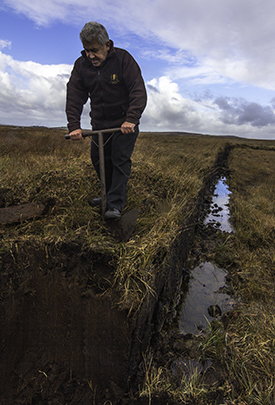 Lagavulin's Iain McArthur cutting peat at his family's bog October 18, 2016. Photo ©2016, Mark Gillespie/CaskStrength Media.