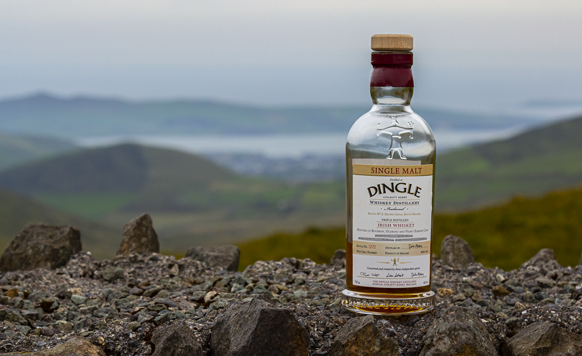 A bottle of Dingle Whiskey on a wall overlooking the town of Dingle, Ireland. Photo ©2019, Mark Gillespie/CaskStrength Media.
