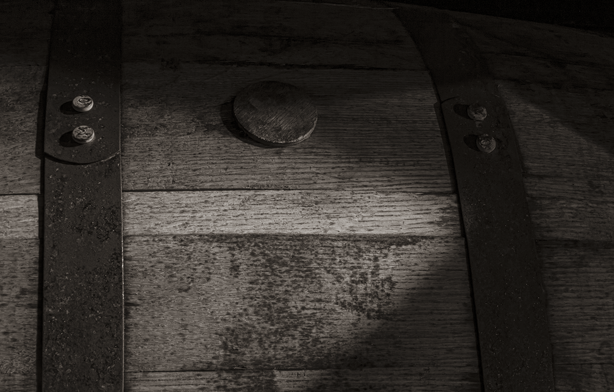 A black and white image of a whiskey barrel maturing in a dark rickhouse. Photo ©2019, Mark Gillespie/CaskStrength Media.