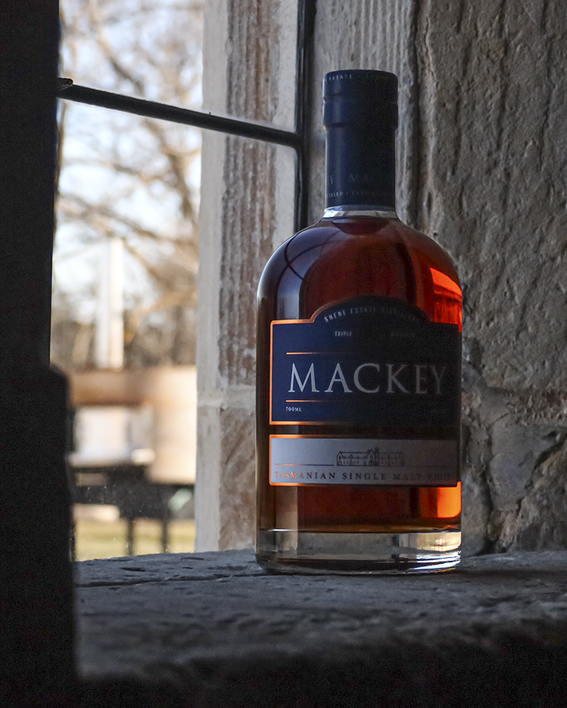 <em>Mackey Tasmanian Single Malt is distilled on the historic Shene Estate in Australia, and this bottle resting on the window sill of one of the estate's historic buildings is our Whisky Photo of the Week.
