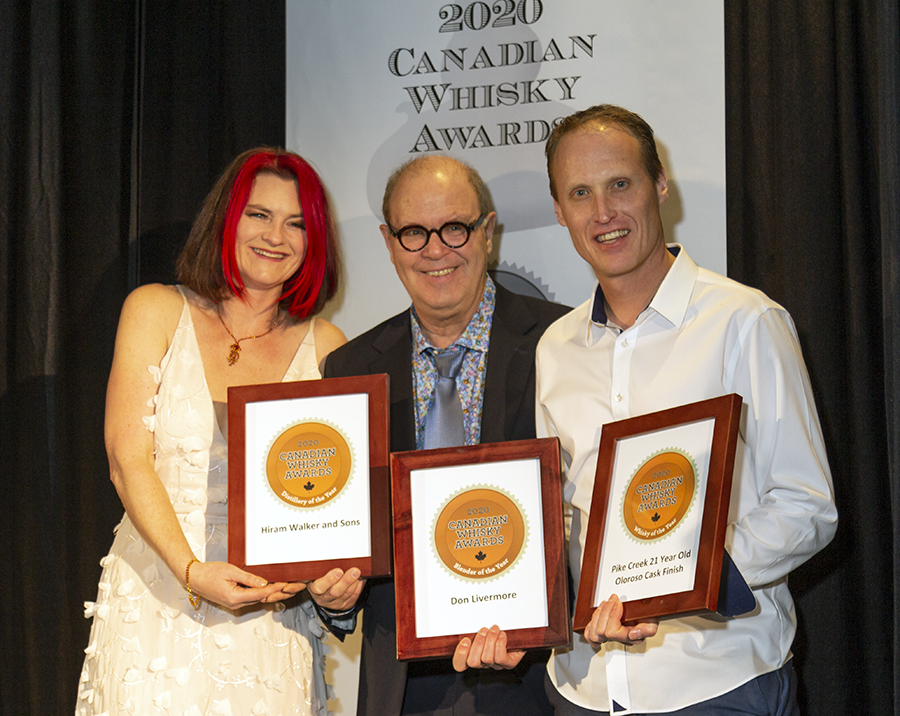 Hiram Walker Distillery took top hono(u)rs at the 2020 Canadian Whisky Awards presentation during the Victoria Whisky Festival. Presenter Heather Leary, Canadian Whisky Awards chairman Davin de Kerghommeaux, and Hiram Walker master blender Dr. Don Livermore showed off the awards for Canadian Whisky of the Year, Distillery of the Year, and Blender of the Year following the ceremony. Photo ©2020, Mark Gillespie/CaskStrength Media.