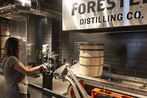 A visitor presses the button to start charring a whiskey barrel in the cooperage at the Old Forester Distillery on Whiskey Row in Louisville, Kentucky. File photo ©2020, Mark Gillespie/CaskStrength Media.