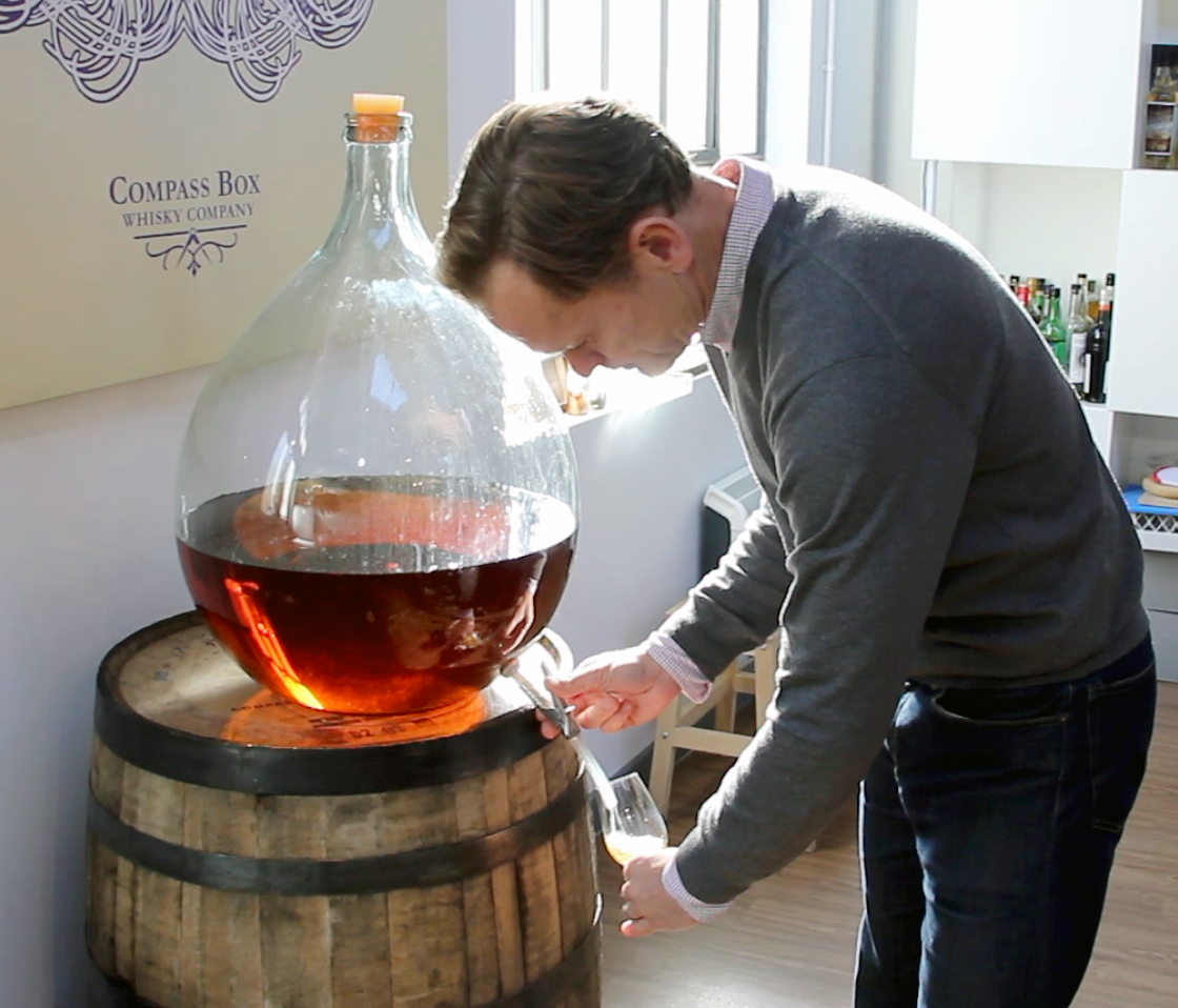 Compass Box Whisky founder John Glaser pours a dram from one of the glass demijohns used for holding samples in the Compass Box blending lab in London. File photo ©2020, Mark Gillespie/CaskStrength Media.