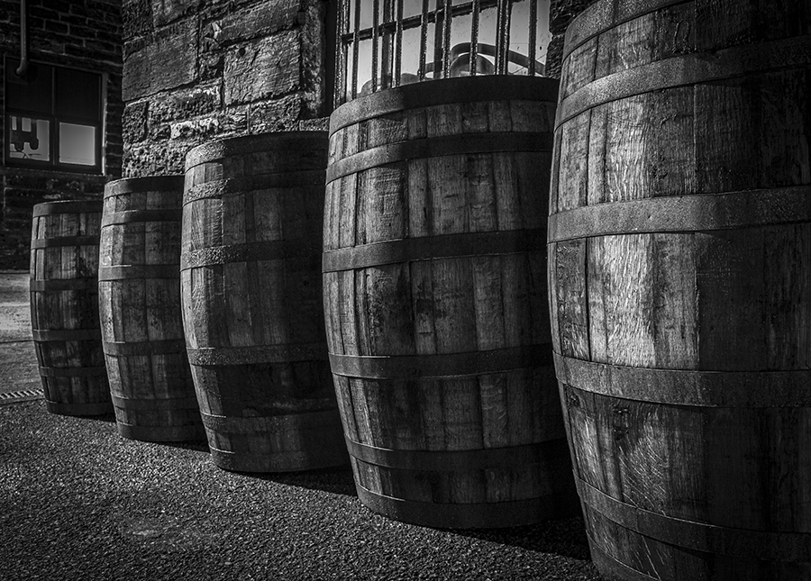 Most people don't get the chance to look around distilleries at night, when the shadows can take an ordinary row of barrels and emphasize the texture in both the wood of the barrels and the stone walls of the Pulteney Distillery still house in Scotland.